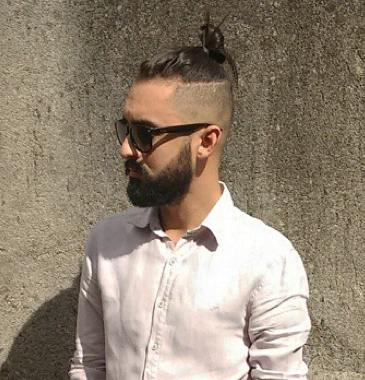 A-picture-of-a-man-bun-undercut-from-a-hipster-wearing-sunglasses-and-standing-next-to-a-wall.jpg