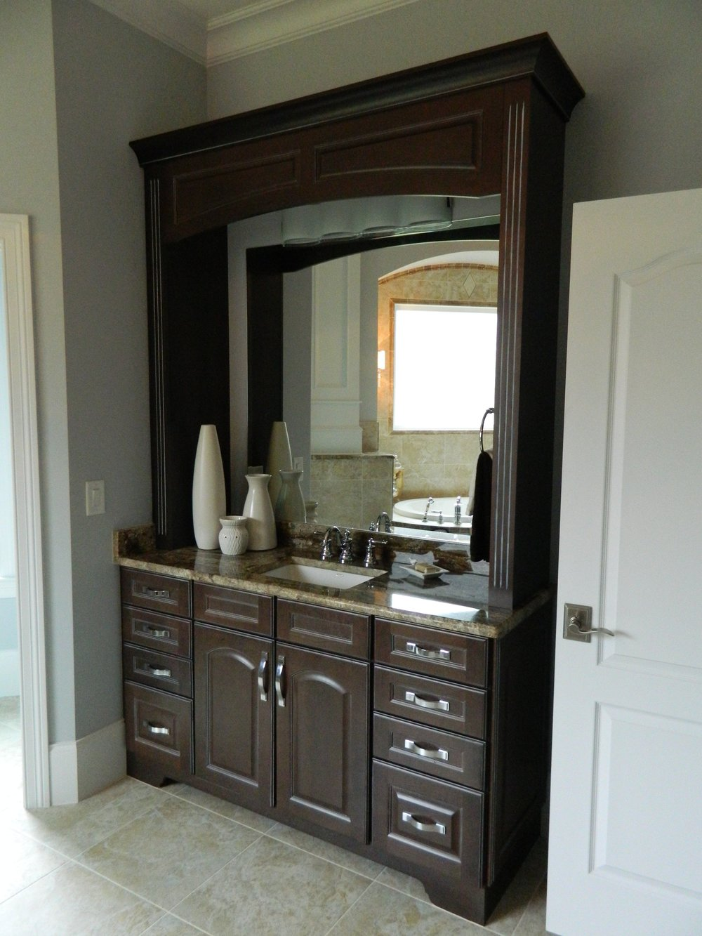 Stain grade vanity with decorative toekick, arched raised panel doors, upper fluted header detail and mirror.