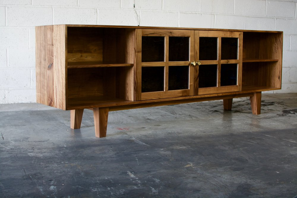 Walnut media unit with glass panel doors.