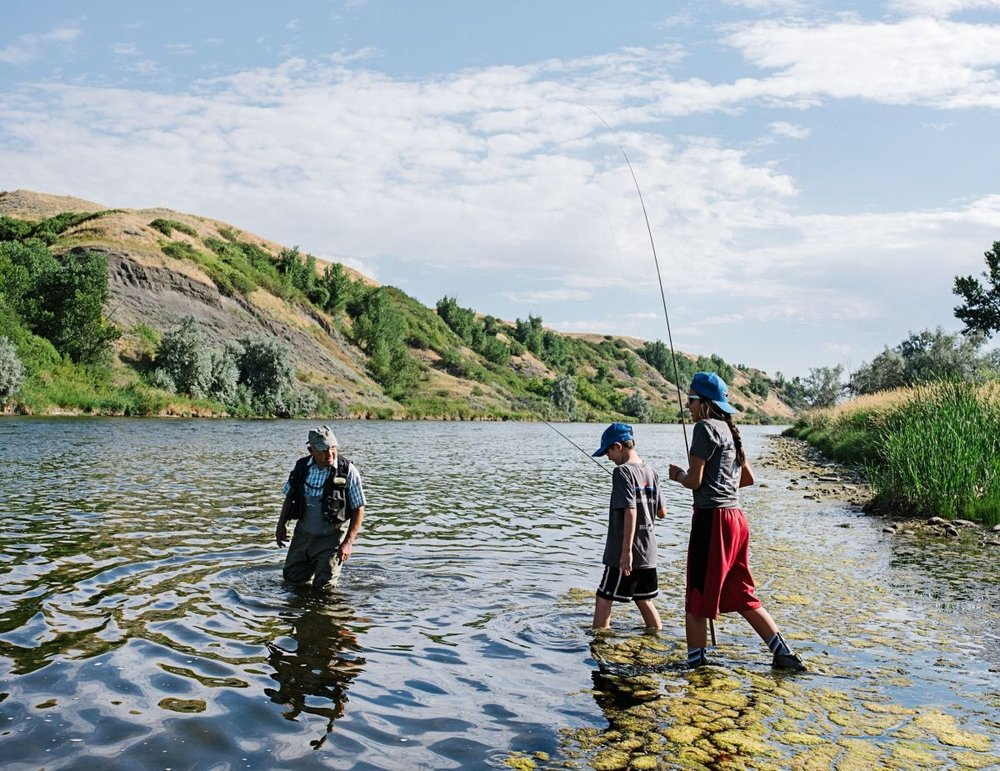 Yvon Chouinard showing Crow children how to fish in Montana. He has frequently disappeared for months, sometimes for half the year, to fish, climb, kayak, surf, ski—and preserve—the planet's untamed precincts.PHOTOGRAPH BY JOHN FRANCIS PETERS FOR THE NEW YORKER