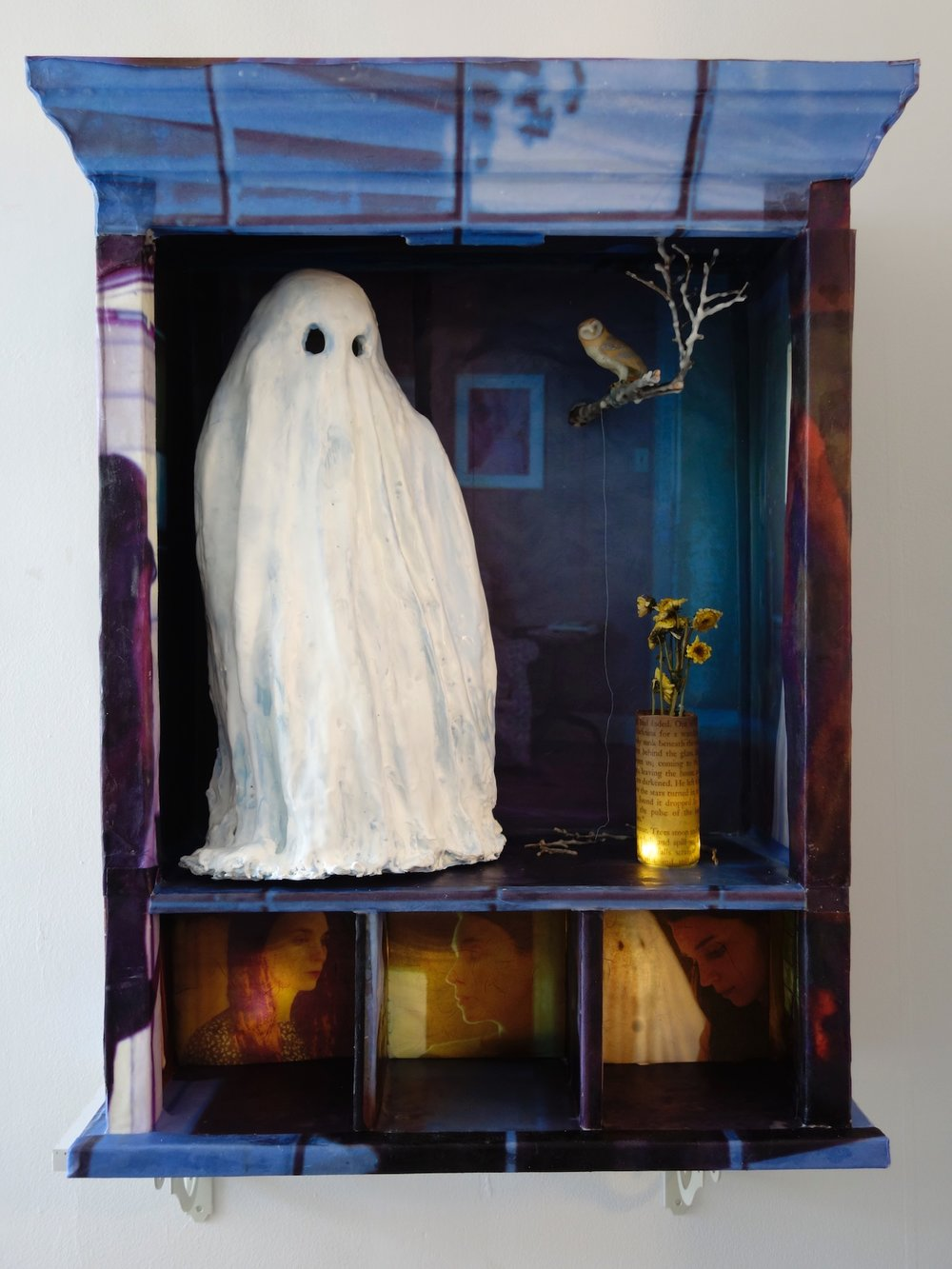 "A Ghost Story, 2018, 30""x24""x10"", screen grabs from the film printed on paper and attached to a wall cabinet with encaustic. Branch, bottles, lights and a toy animal. $3,000"