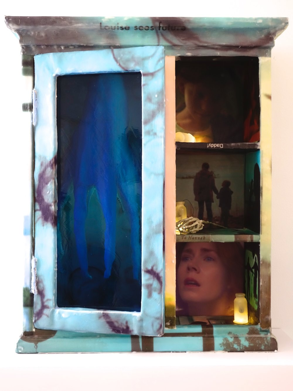 "Arrival, 2018, 20""x24""x9"", screen grabs from the film printed on paper and attached to a wall cabinet with encaustic. Branch, bottles, lights and a toy animal. $2,000"