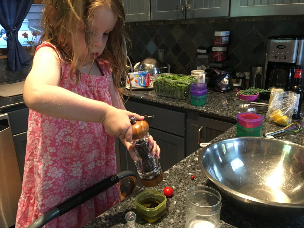 Then quite seriously, she told me that we make the dressing first before chopping. First she poured the oil into our kid friendly shaker cup. Then she cranked the pepper.