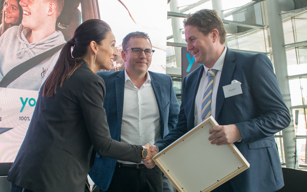 Prime Minister Jacinda Adern presents YHI's Aaron Gillon with a Foundation Partner acknowledgement at the Yoogo Share Launch.