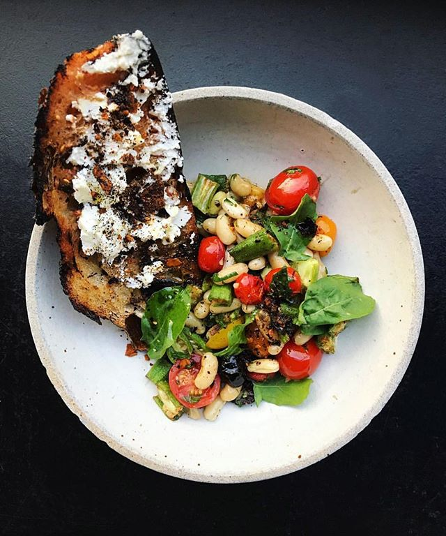 Cannelini beans, tomatoes, okra, and arugula pesto served with goat cheese toast dusted with dry mole 📷: @chefjosefcenteno