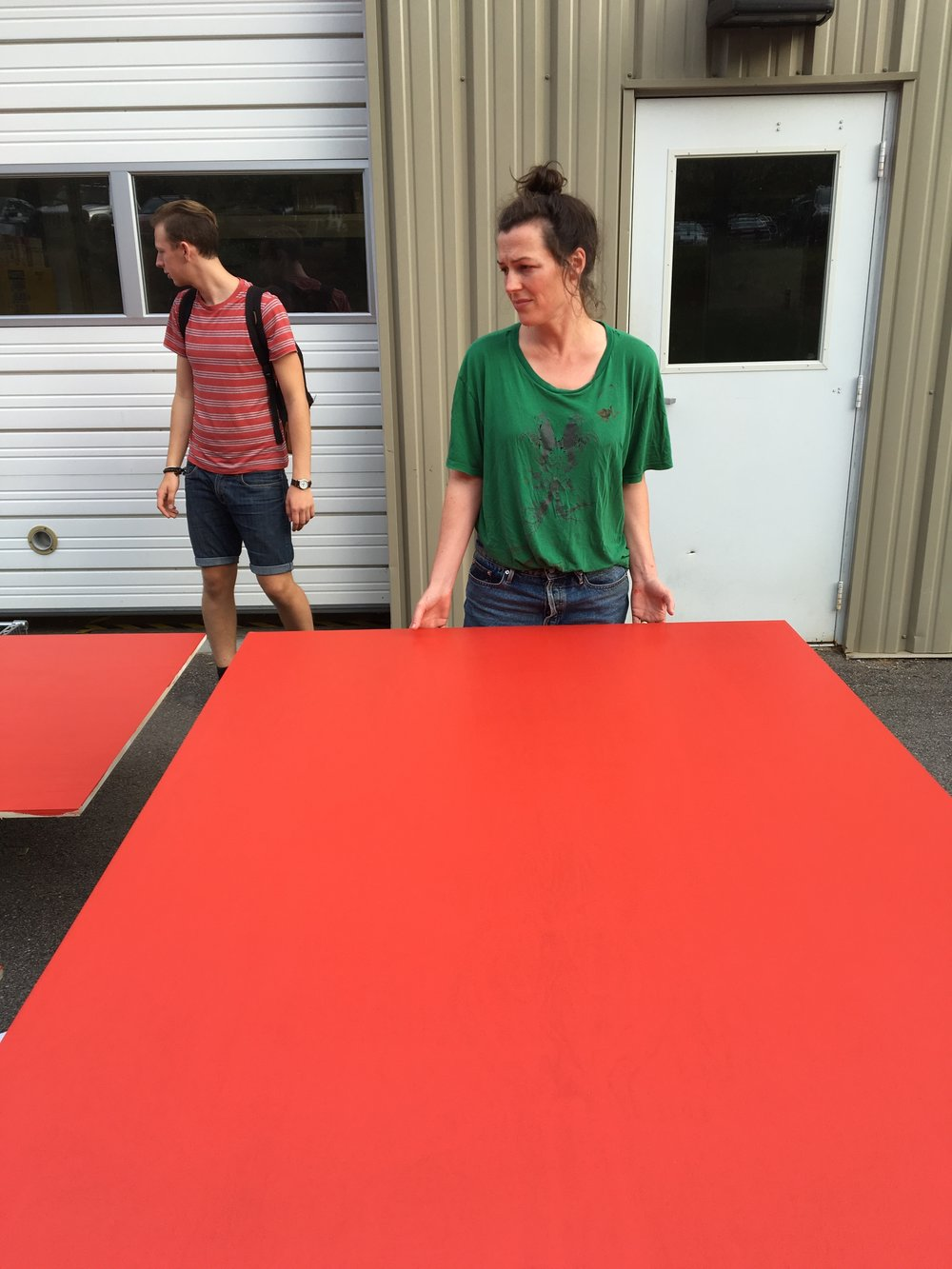Sara moving a freshly-painted plywood sheet.