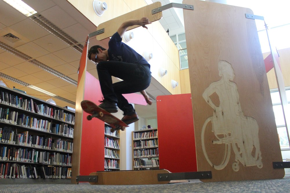 Tim testing out one of the skateboarding/wheelchair access ramps in the installation.