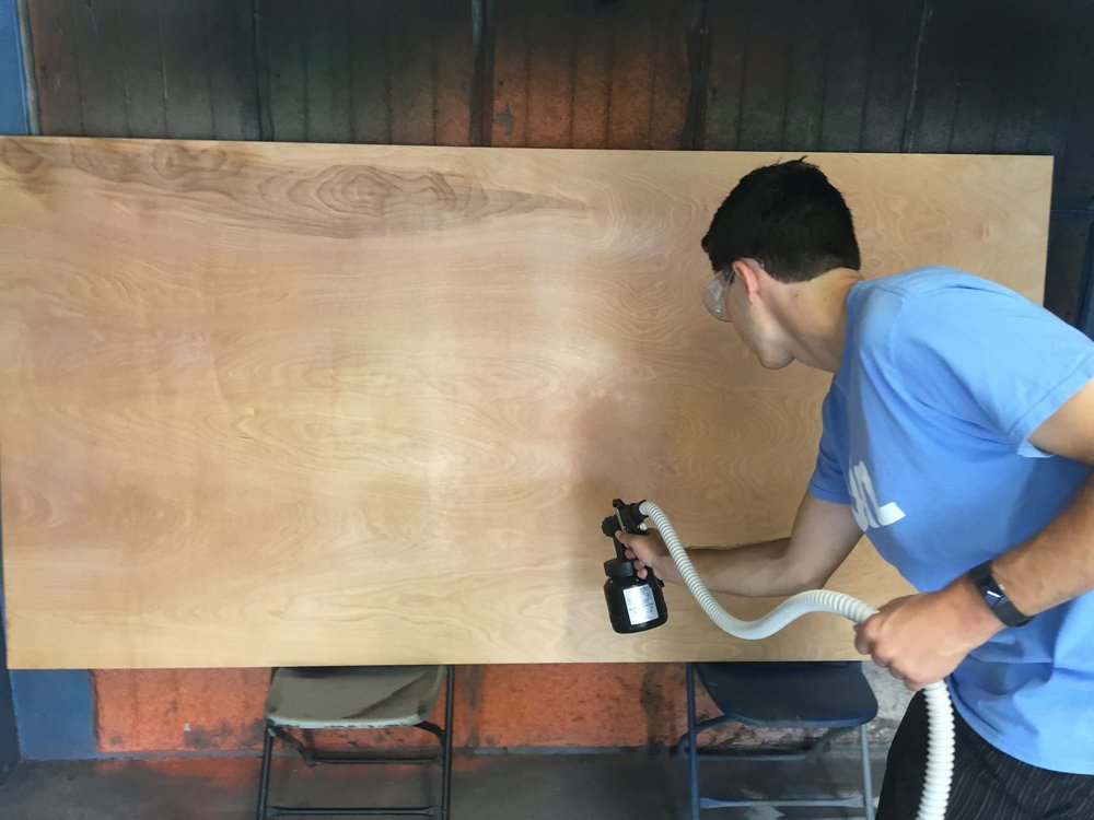 Keenan applying finish to a plywood sheet.