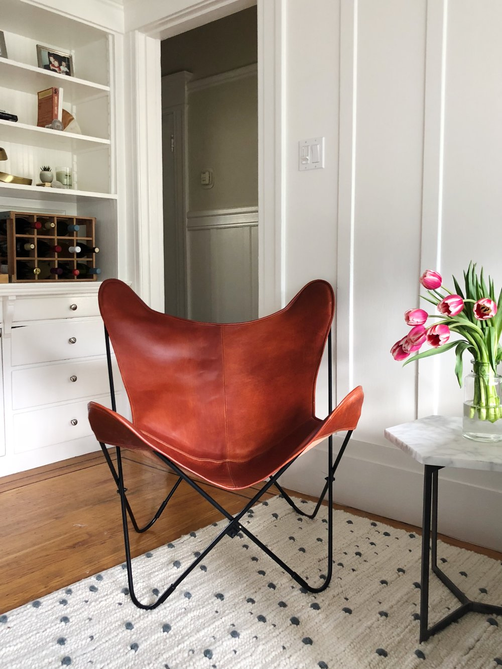 Leather chair:  The Citizenry . Rug:  CB2 . Marble side table:  West Elm . Wine rack:  Crate and Barrel .