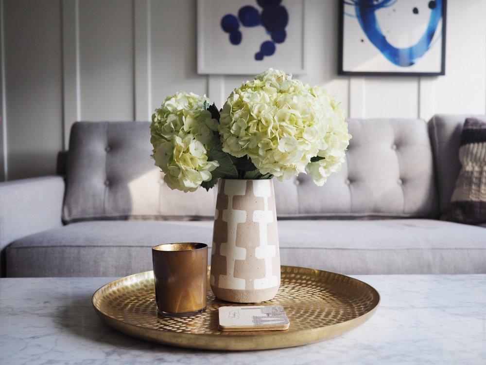Grey couch:  West Elm . Ceramic vase:  Target . Brass tray:  Target . Candle:  Cire Trudon . Blue print (left): Minted. Blue print (right):  Minted .