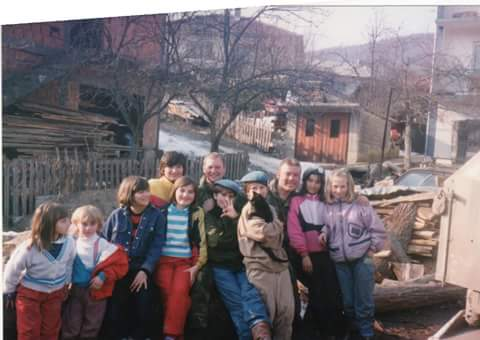 Pictured here are the children from the neighborhood with two UN soldiers. It's just one of those moments that made you feel happy and content. They even allowed us the honor of wearing their blue berets, which symbolized peace. (1993, Kladanj)