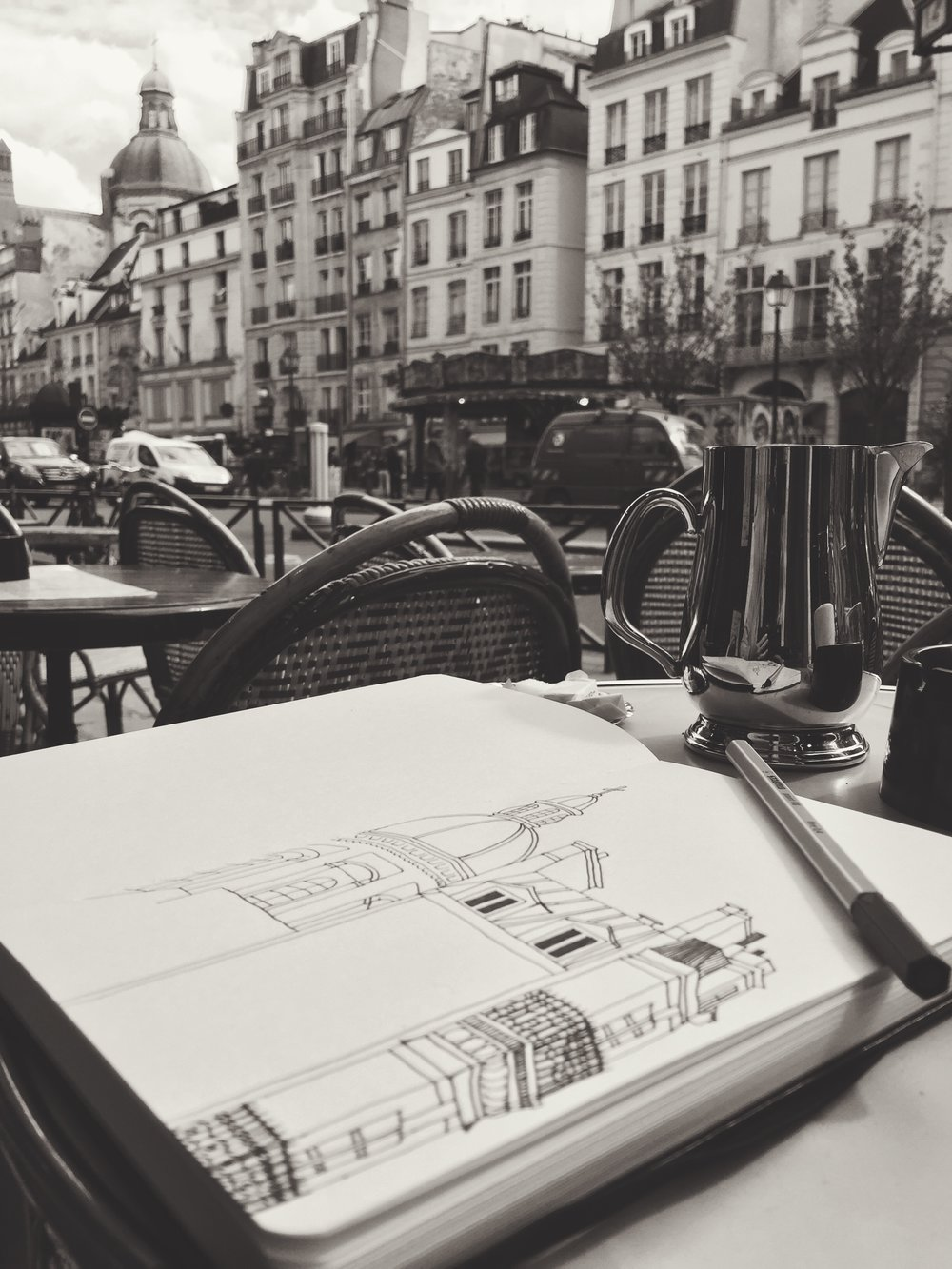 Sketching the skyline of Paris with an afternoon coffee