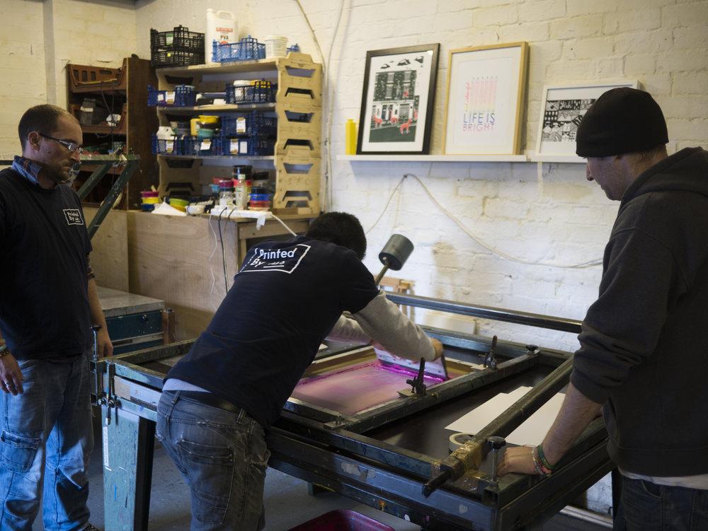 ABOVE: James, Hugo and Craig hand screen printing the 'Glass Half Full' A3 Artwork print