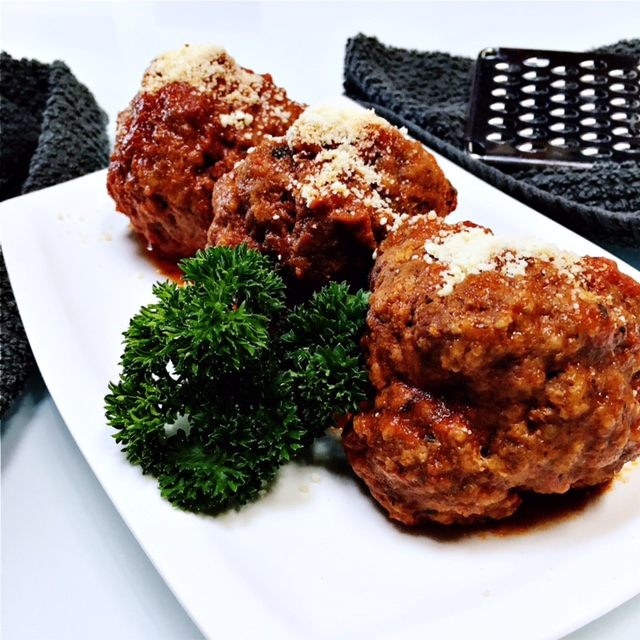 Meatballs in marinara sauce, topped with parmesan cheese and ready to be enjoyed!