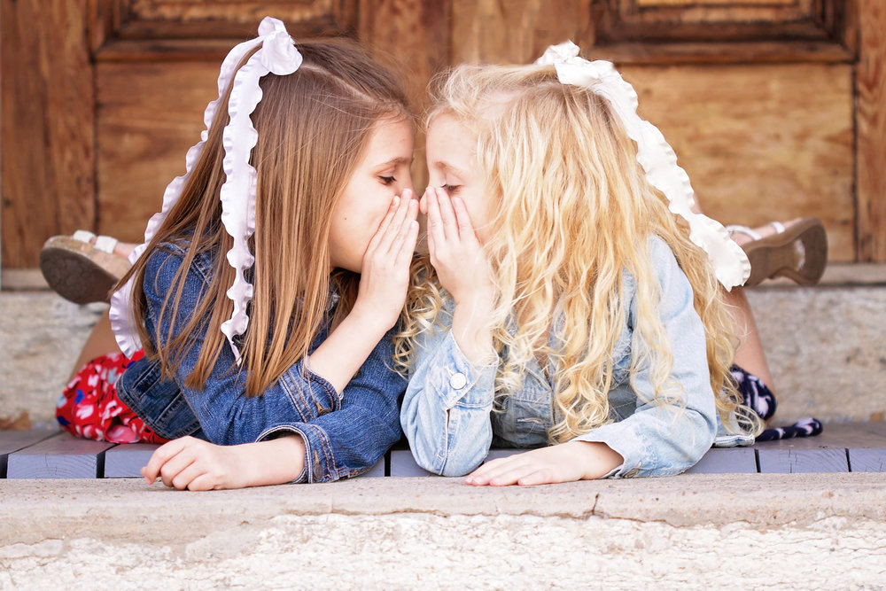 two little girls with bows whispering.jpg