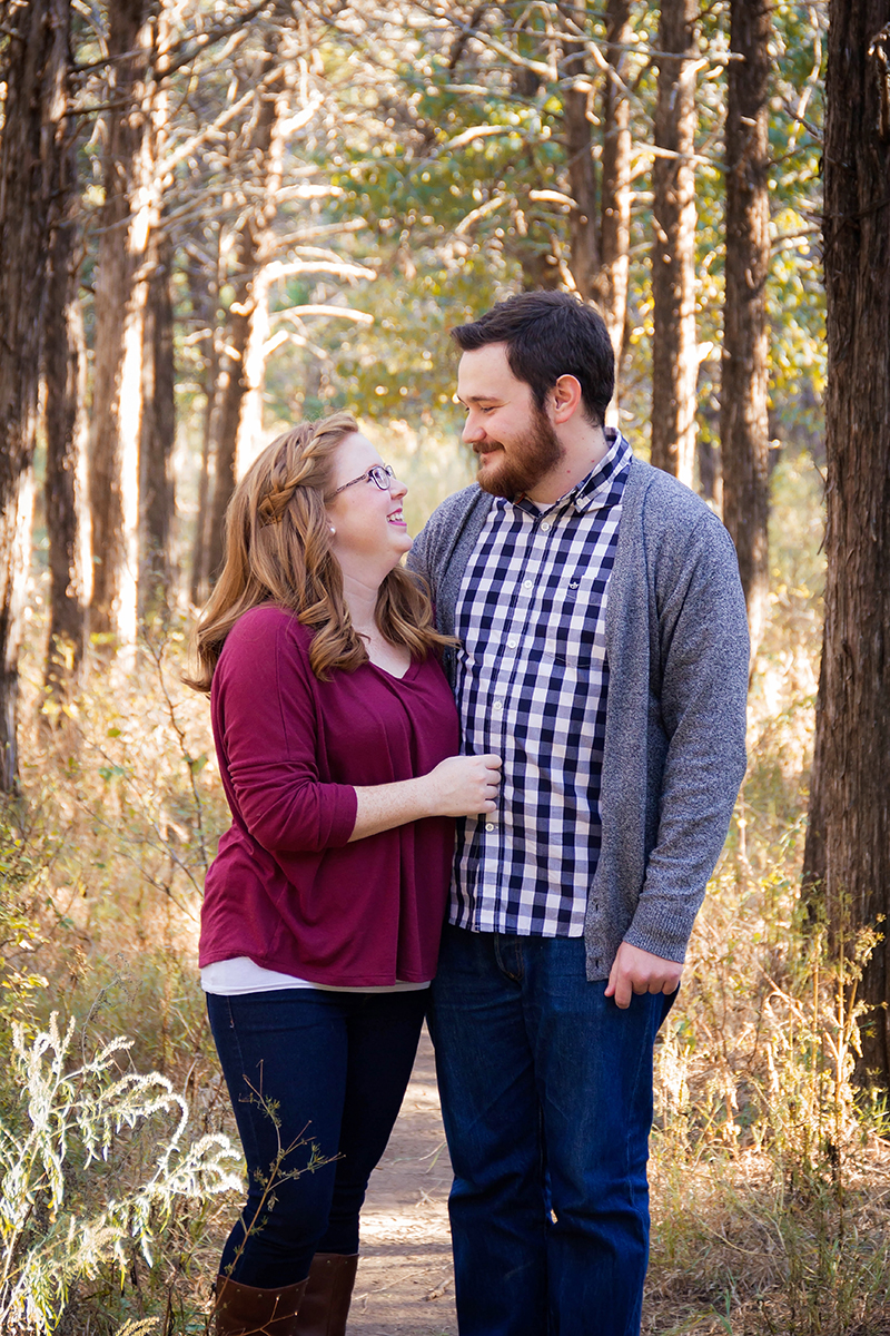 Cute couple in purple and blue plaid standing in forest.jpg