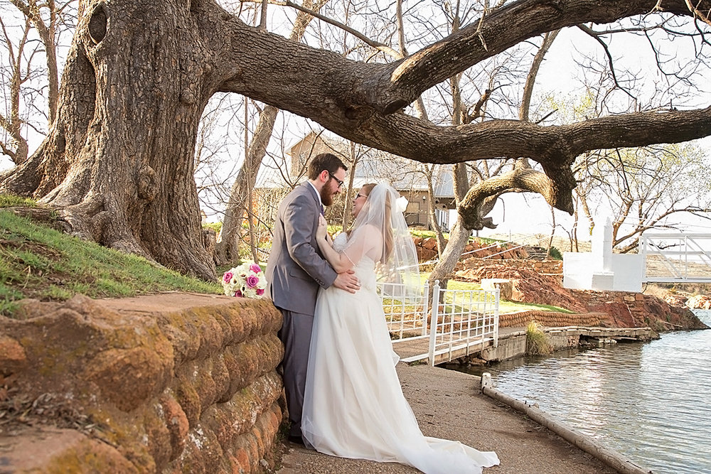Wedding couple standing by river in Medicine Park, OK.jpg