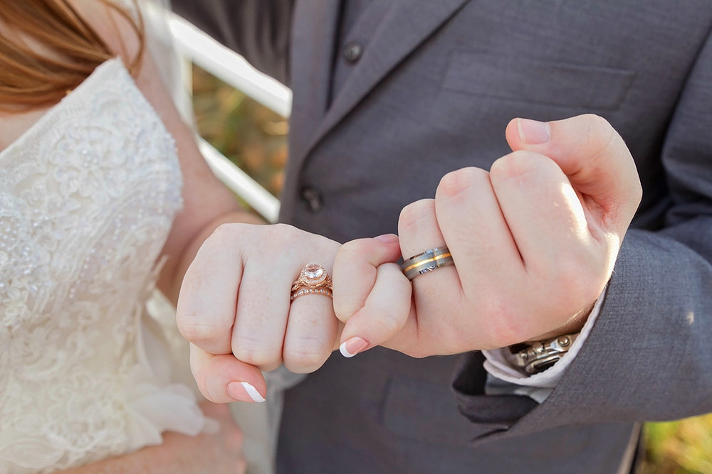 Bride and Groom holding pinkies showing rings.jpg