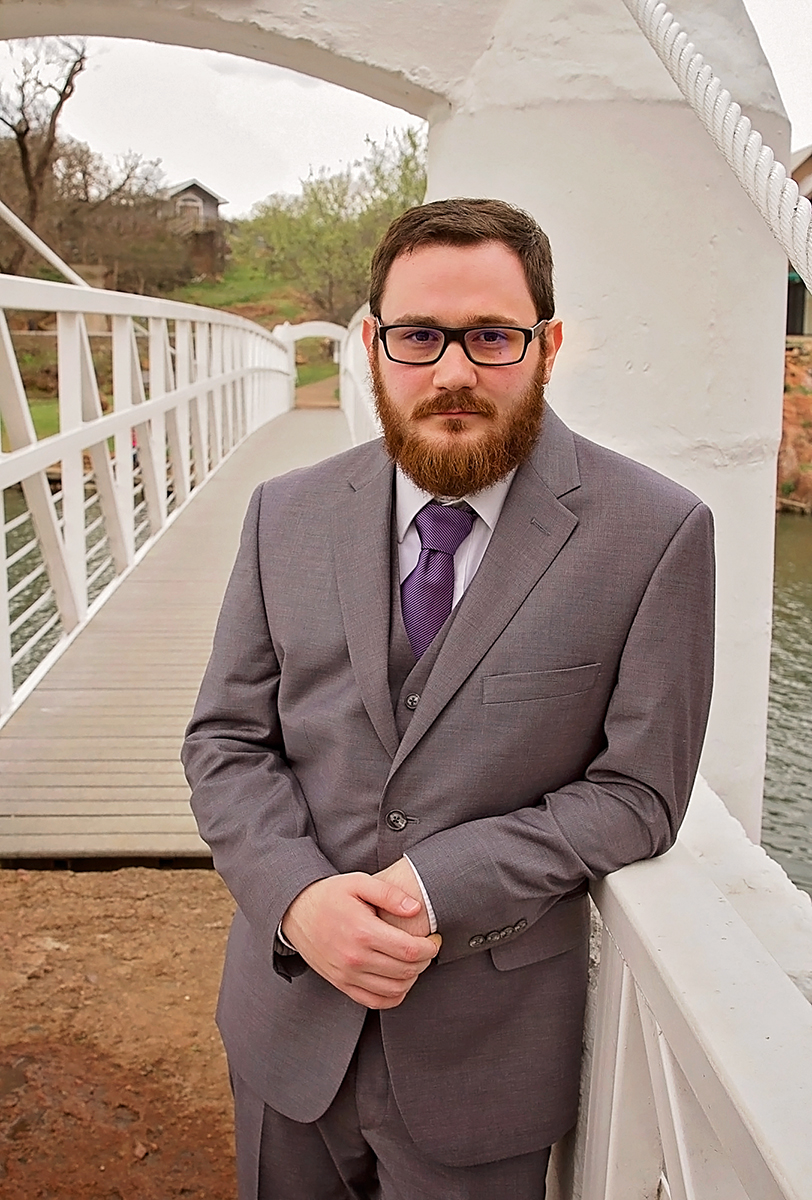 Groom standing by bridge in Medicine Park, OK.jpg