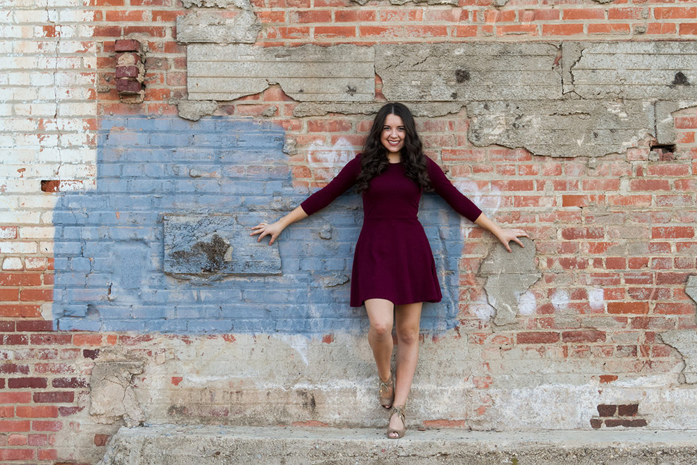 Senior Girl in Red Dress holding onto brick wall.jpg