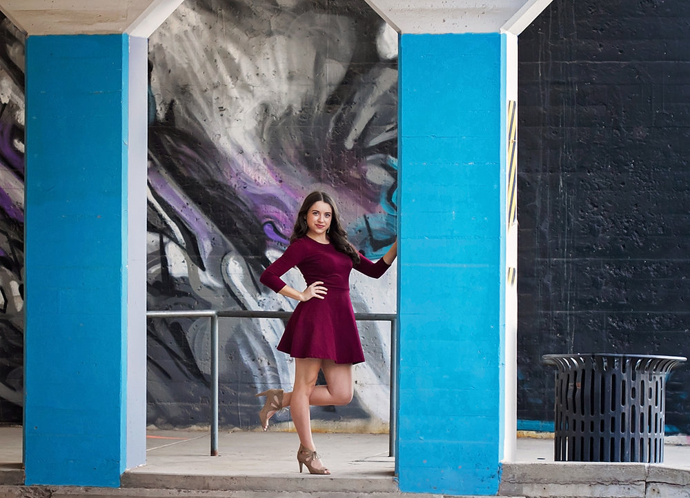 Senior Girl in Red Dress Standing under an underpass mural.jpg