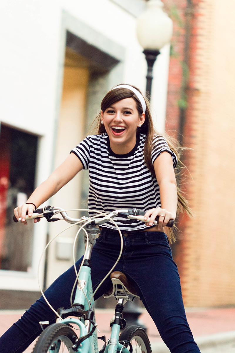 Audrey Hepburn styled session girl riding bike and smiling.jpg