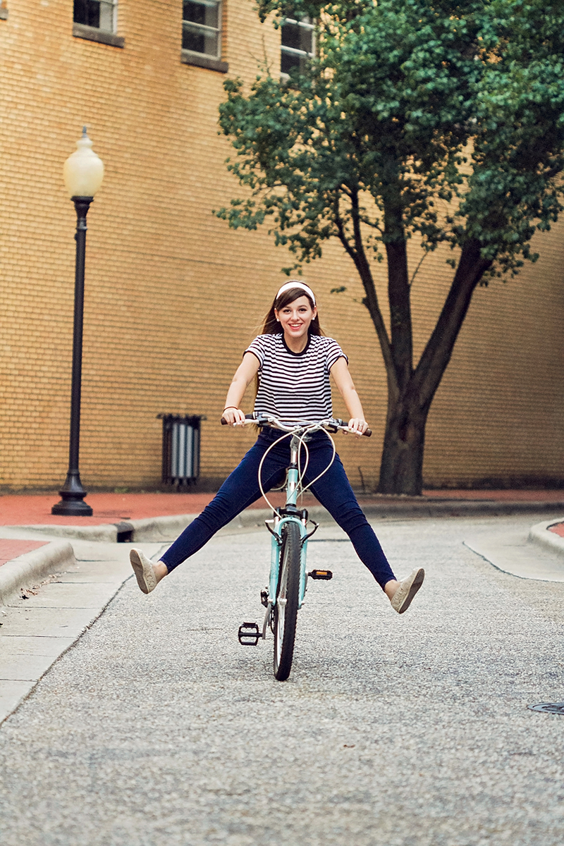 Audrey Hepburn styled session girl riding bike down street.jpg