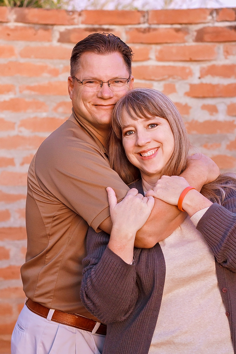 Portrait of Couple in Tan and Gray hugging.jpg