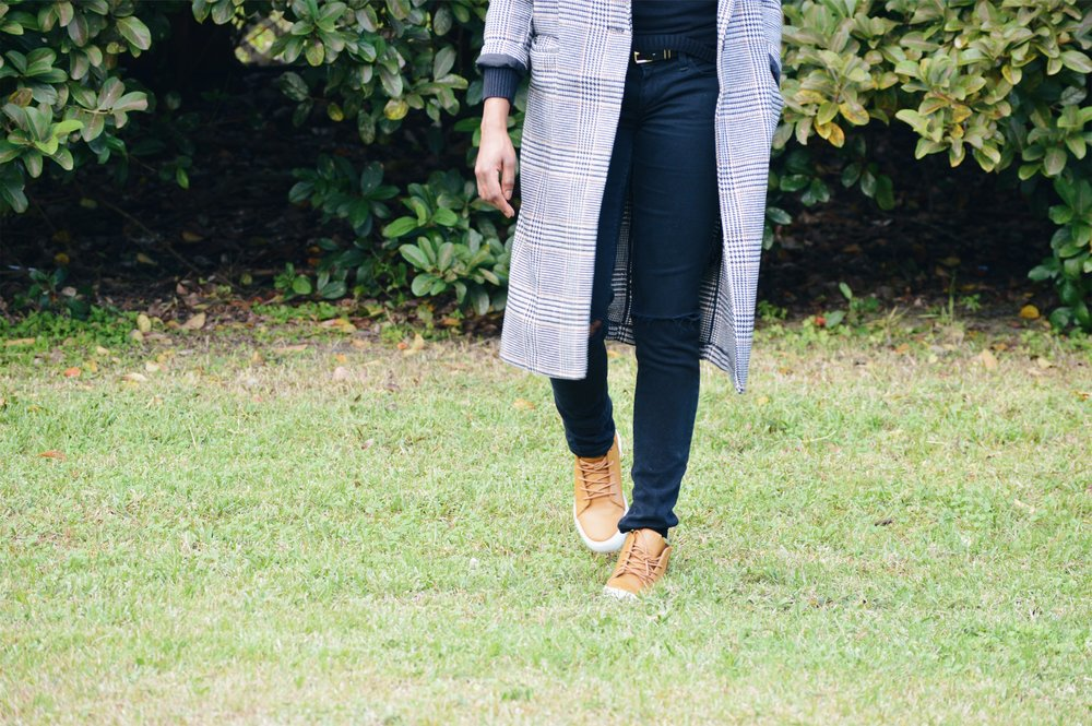 hm long plaid coat black turtle neck black distressed jeans tan sneaker natural hair