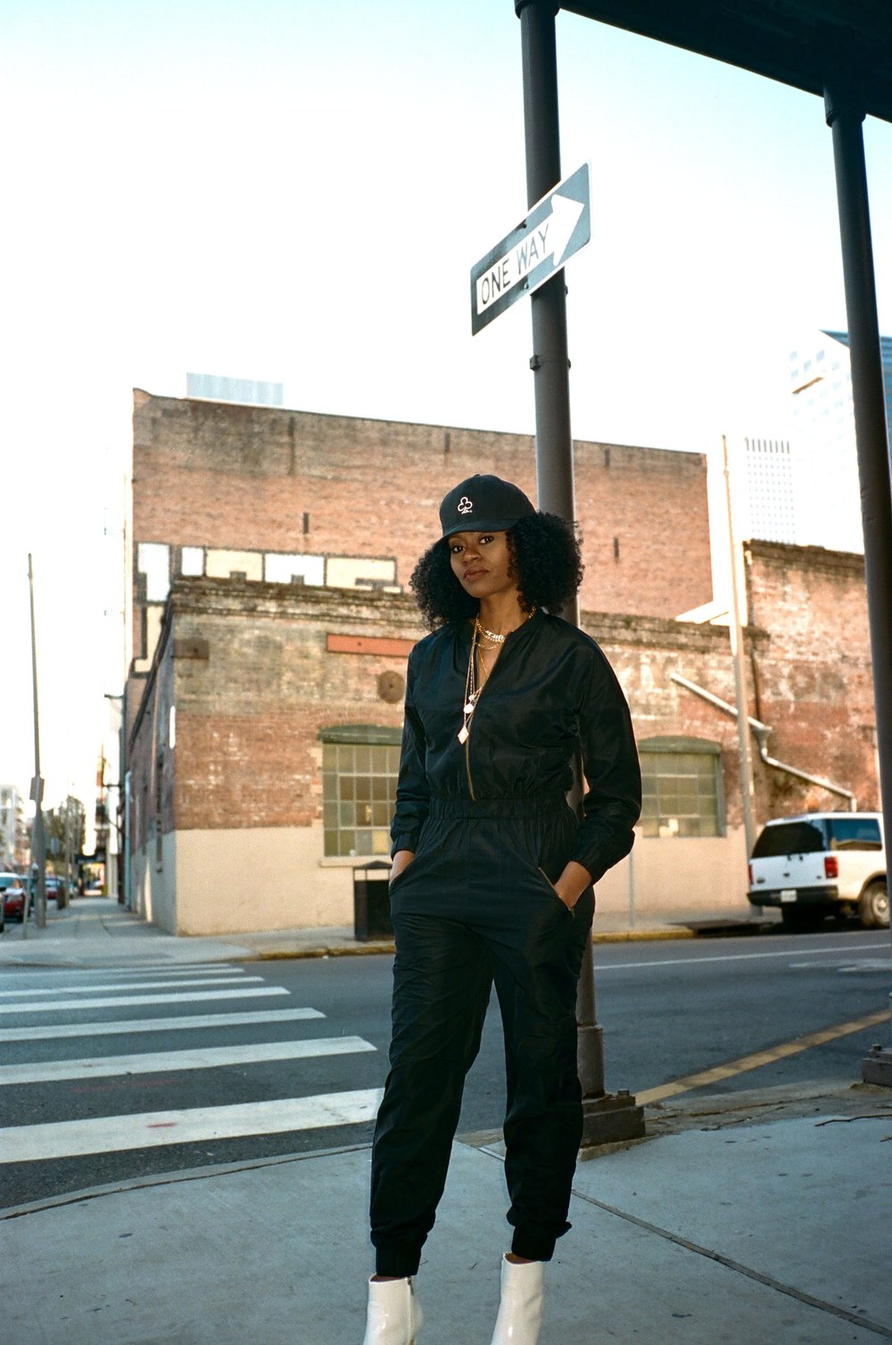 black jumpsuit with white boots the loyalty club hat anarchy street layered necklaces