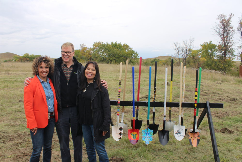 Tawney Brunsch (Oglala Lakota), Executive Director of Lakota Funds; Kelley Lindquist, President of Artspace; and Lori Pourier (Oglala Lakota), President of First Peoples Fund stand beside shovels designed by local artists. The organizations have partnered to form Oglala Lakota Artspace, LLC and will collaboratively oversee the facility.