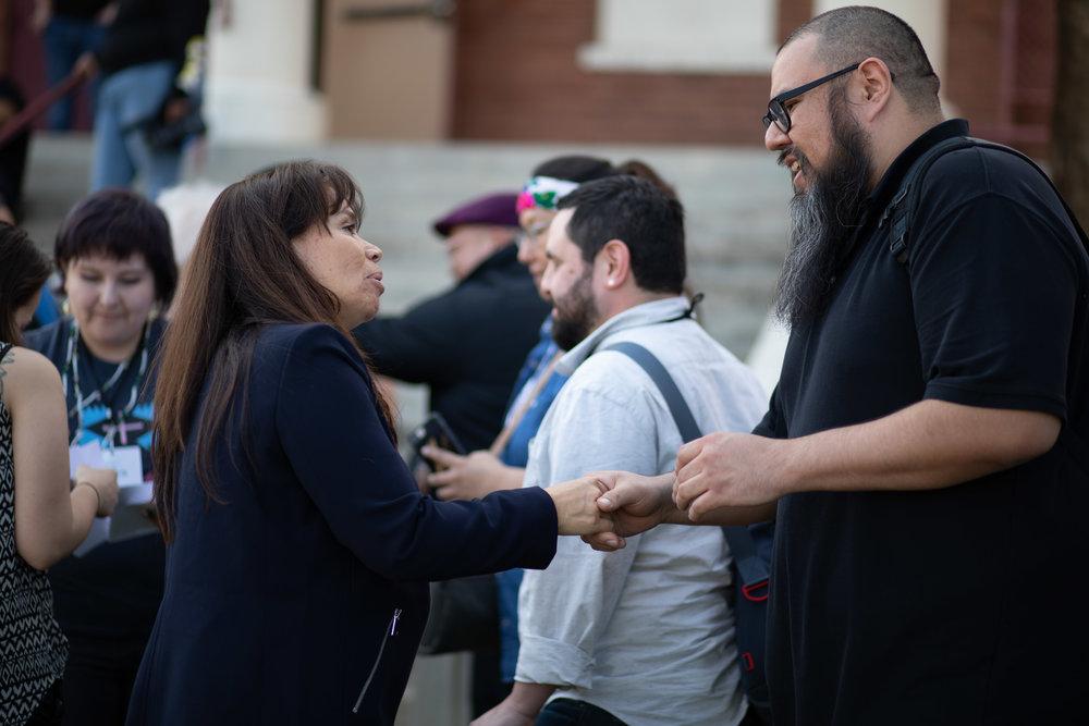 FPF President, Lori Pourier (Oglala Lakota) shakes hands with site manager for IAE Grant Program partner, 4-Directions Development, Peter Mckenzie.