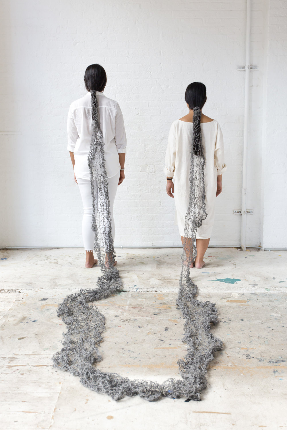 Image of Swati Kapur and the artist with the back to their backs to the camera, showing their long black hair being tied together by the steel wool yarn. The steel wool blanket flows from Swati's hair to the floor to the artist's hair.