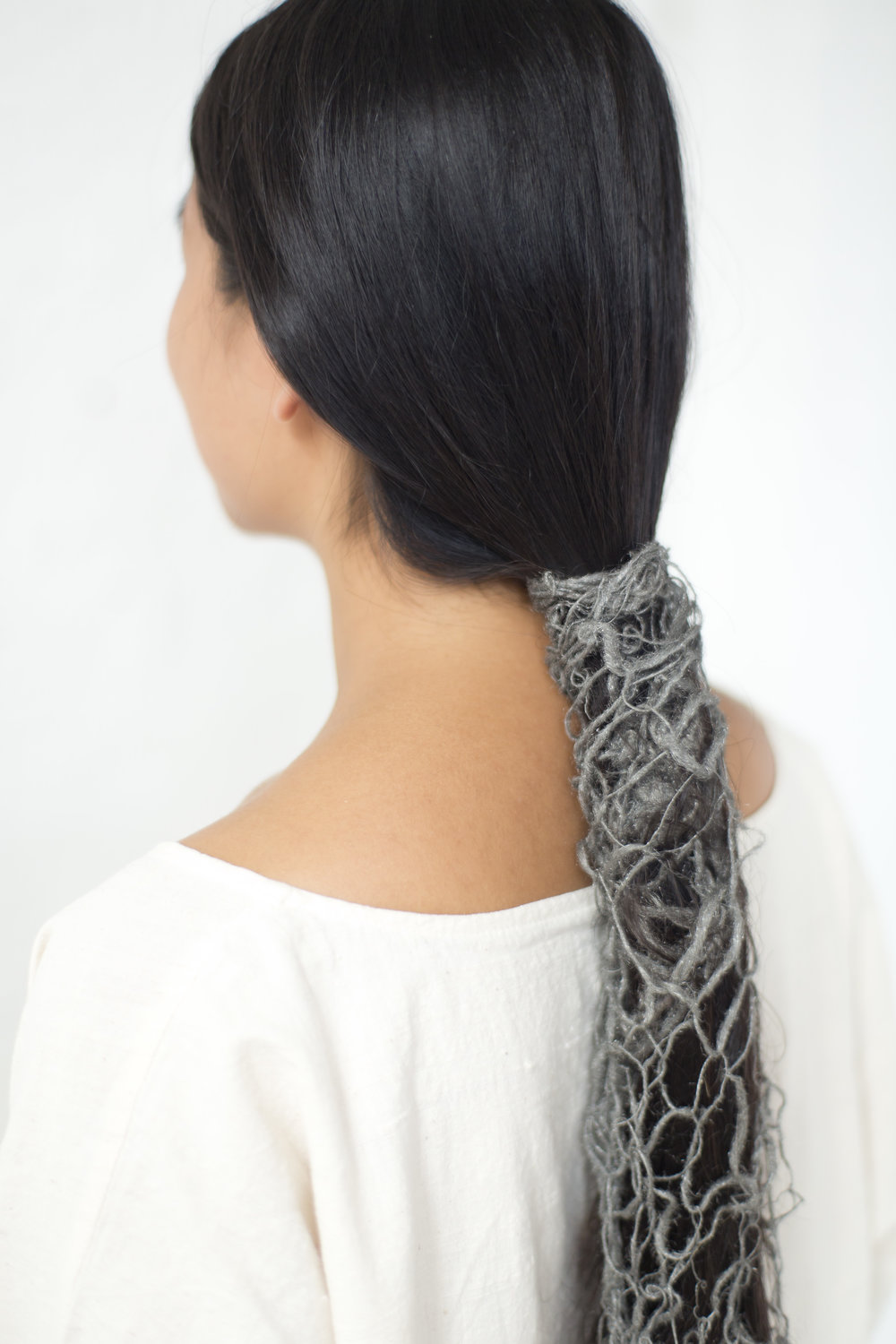 A detail photograph of the steel wool blanket wrapping around the artist's hair.