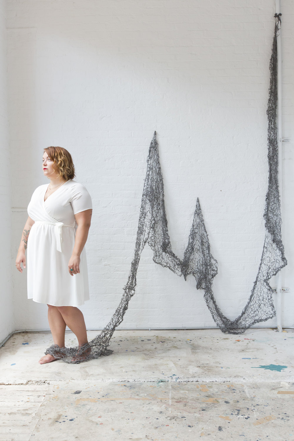 Image of Kate Bernyk looking outside the window with the steel wool blanket tying around her ankles. The image resembles a fisherman's net with the steel wool blanket being held up at points on the wall to showcase the dip in the material.