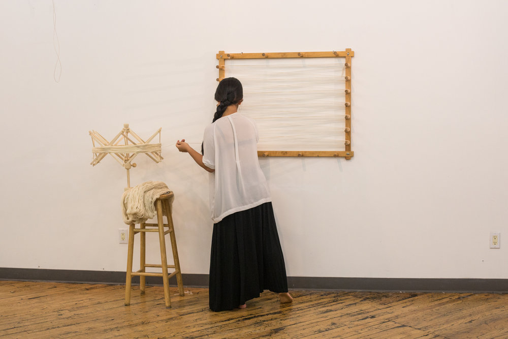 Artist winding the yarn from a swifter positioned on a stool onto a warping board on the wall. The stool also holds the six skeins of yarn. Her back is to the audience.