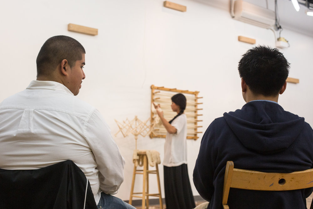Two audience members watching the performance with the artist blurred in the background. She is counting the number of times the yarn is wrap around her hand as a representation of days.