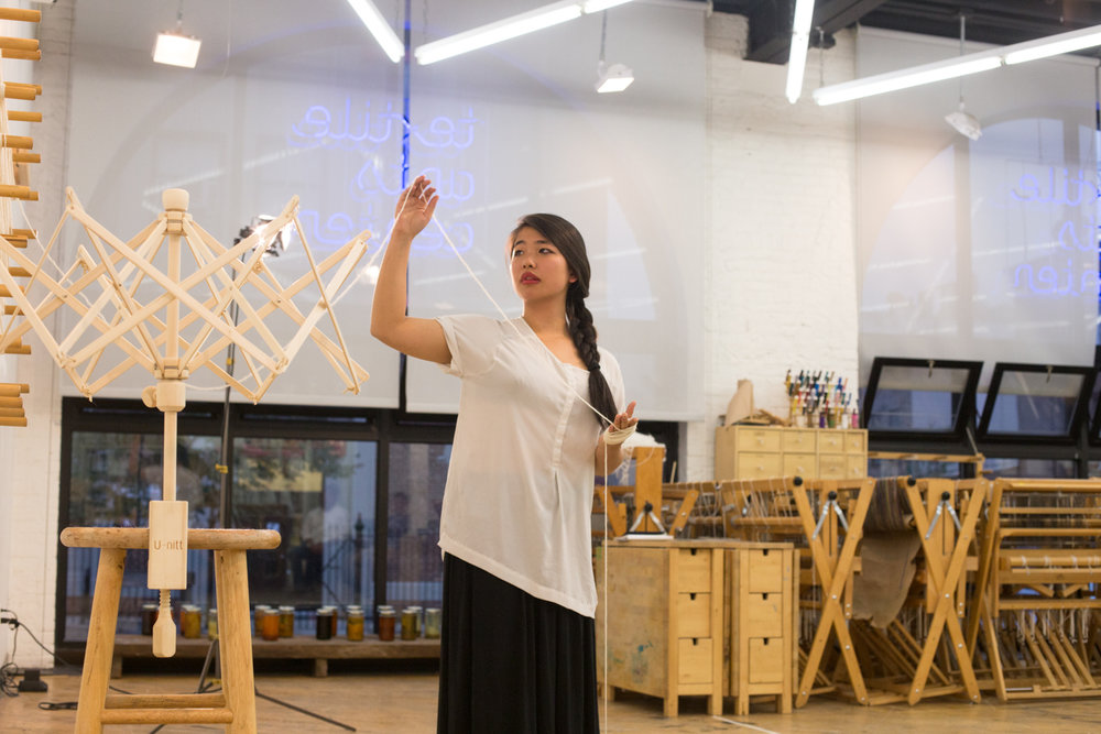 Artist tugs on the yarn from the warping board to continue wrapping it around her hand.
