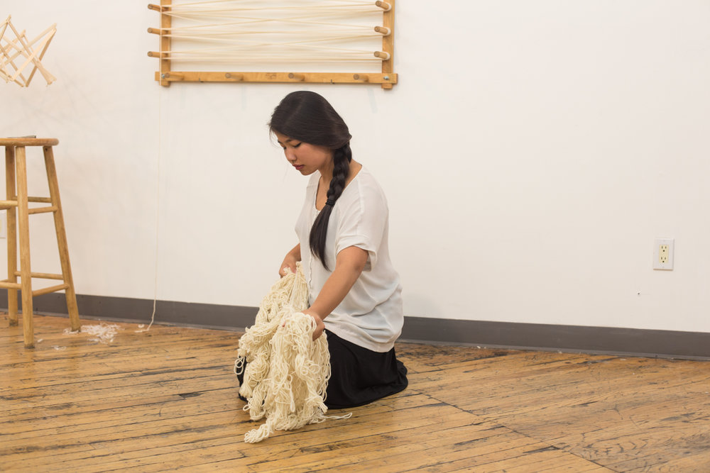 The artist kneels on the floor and continues to create more knots with the yarn.