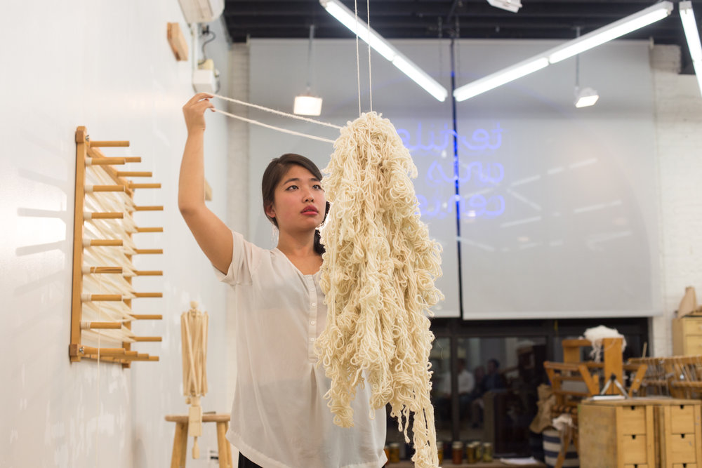 The heap of knotted yarn is picked up from the floor and suspended in the air by a string hung from the ceiling. The artist begins to unknot and unravel the yarn that she has knotted previously.