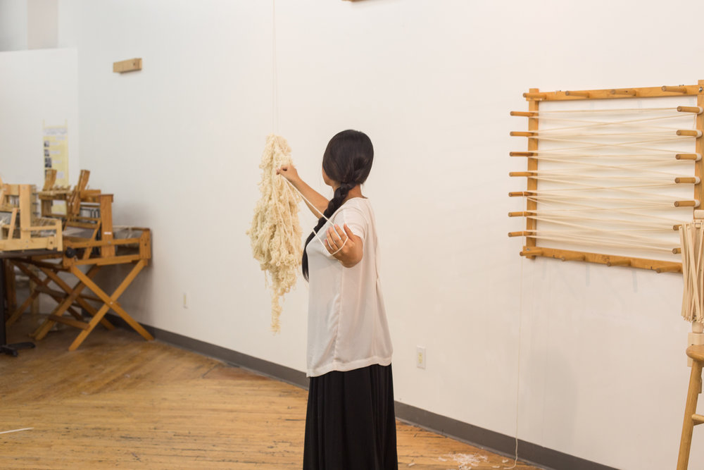 The artist is standing with her left arm stretched back to create a loop in order to unravel the yarn. Her back, the suspended yarn, the warping board, and part of the stool and the swift are visible.
