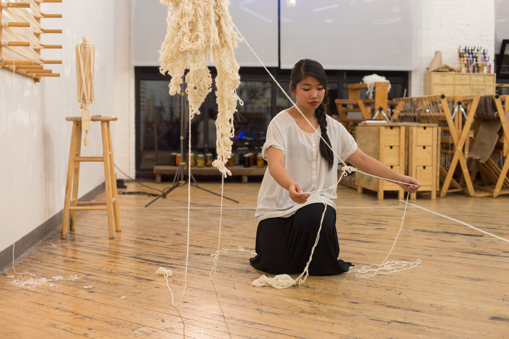 The artist untangles a knot as she kneels on the floor.