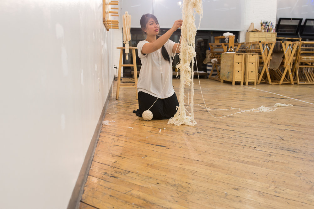 The ball of untangled yarn (around 2 inches in diameter) is on the floor as the artist kneels and continues to untangle. Her hair is a little disheveled.