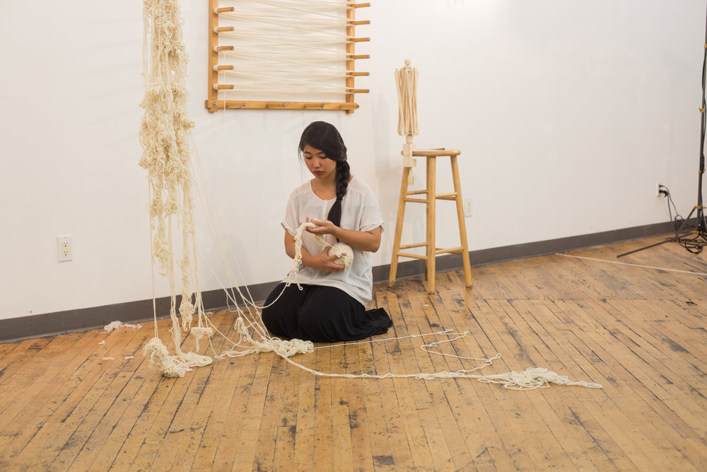 The artist holds the ball of untangled yarn (around 3.5 inches in diameter) close to her body as she continues to untangles. There is still half of the knotted yarn being suspended. Longer strands of knotted yarn are on the floor.