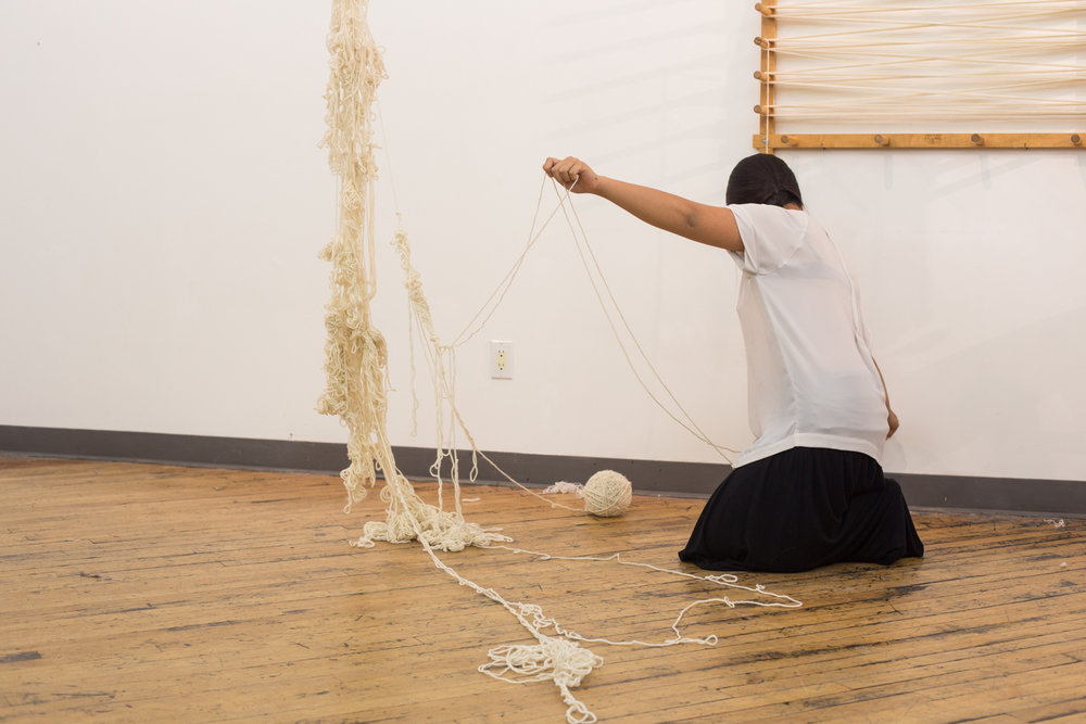 The artist stretches two strands of yarn to create a loop. The ball of untangled yarn is slightly bigger than 3.5 inches in diameter.
