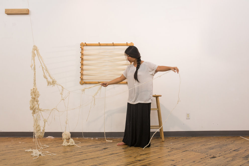 Only one-tenth of the knotted yarn is left. The artist is stretching the larger strands of yarn suspended in the air to create loops.