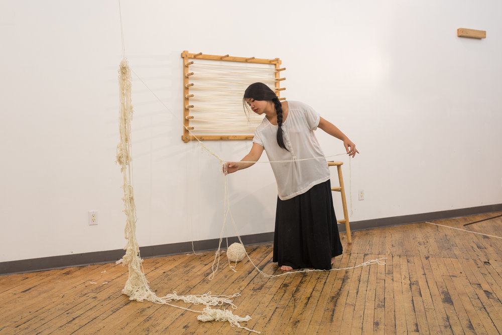 The artist leans in to untangle a knot with the ball of untangled yarn on the floor.