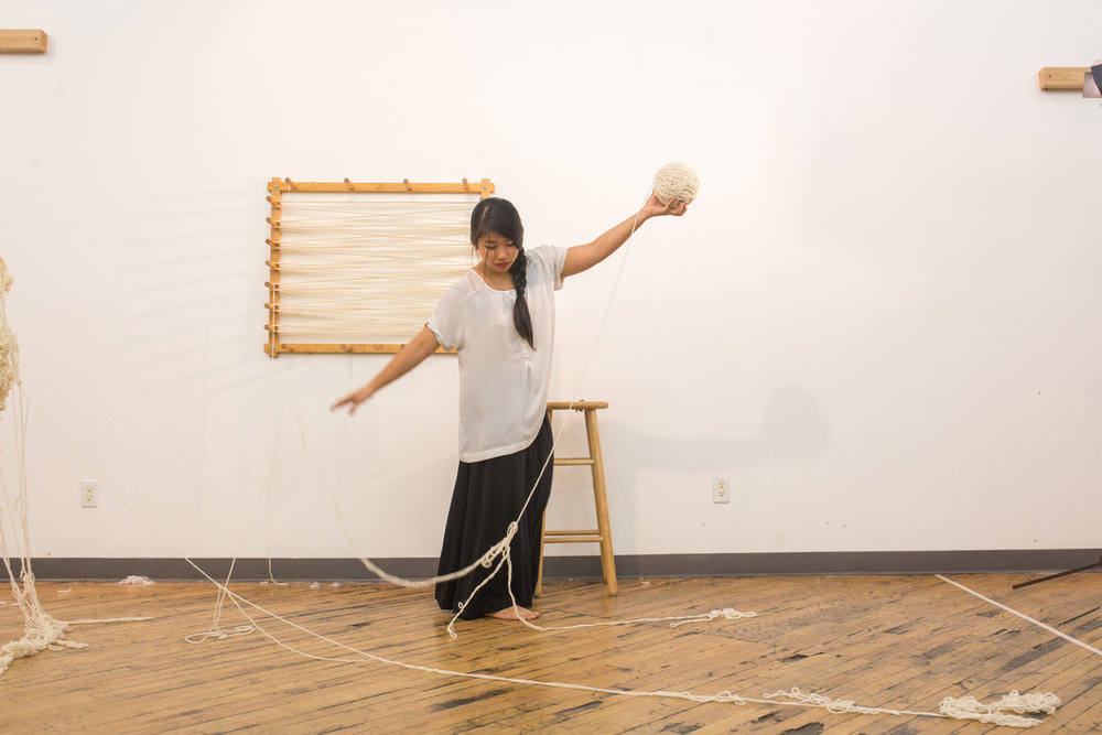 Artist throws the strand of untangled yarn onto the floor with her right hand as she lifts up the ball of untangled yarn with her left hand.