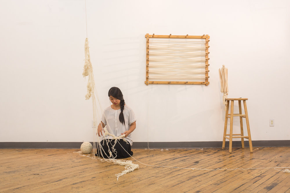 The artist is on the floor. The ball of untangled yarn is now around 7 inches in diameter. One-fifteenth of the knotted yarn is suspended in the air and drapes onto the floor.