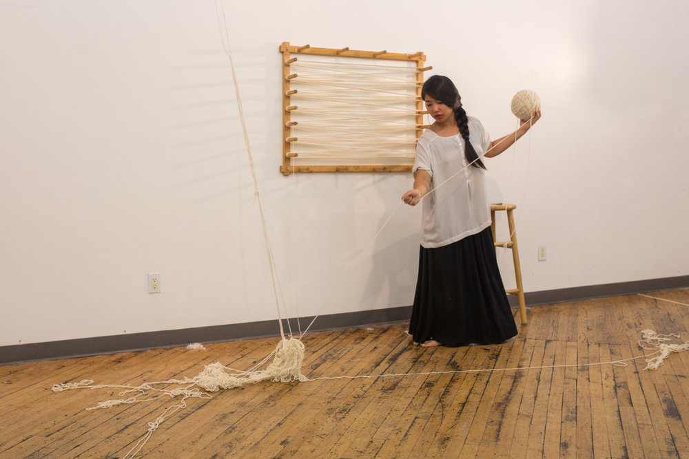 The artist pulls at the heap of knotted yarn as it falls onto the floor.